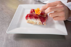 Close up of baker putting flower on the pastry with fruit Royalty Free Stock Photos