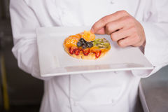 Close up of baker putting flower on the pastry with fruit Stock Images