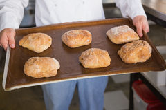 Close up of baker showing tray with bread Stock Photo