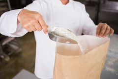 Close up of baker taking flour with a scoop Stock Photo
