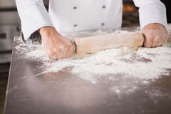 Close up of baker using a rolling pin Royalty Free Stock Photos
