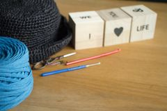 Close up of a ball of bright blue yarn, a black knitted hat and wooden cubes with an inscription in English I love life on a light. Wooden surface. Selective stock image