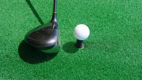 Close up ball on tee retired golfer taking swing hitting golf ball off tee on golf course. Close up ball on tee retired golfer Royalty Free Stock Images