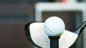 Close up ball on tee retired golfer taking swing hitting golf ball off tee on golf course Royalty Free Stock Photos