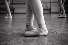 Close-up of ballerina feet on pointe shoes in the dance hall. Vintage photography. Close-up of a ballerina in the dance hall. royalty free stock image