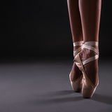 Close up of ballerina legs in pointes ober gray Stock Image