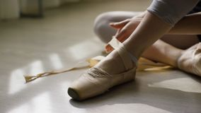 Close-up of ballerina`s feet. Ballerina preparing for training, and tying ribbon of pointe shoes sitting on floor in royalty free stock images