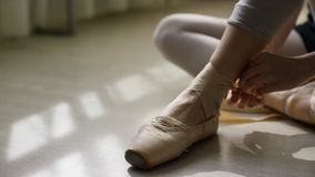 Close-up of ballerina`s feet. Ballerina preparing for training, and tying ribbon of pointe shoes sitting on floor in. Bright sunlight royalty free stock photos