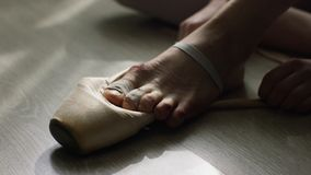 Close-up of ballerina`s feet. Ballerina preparing for training, and tying ribbon of pointe shoes sitting on floor in royalty free stock image