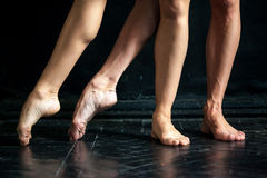 Close-up ballerina's legs on the black wooden Royalty Free Stock Images