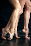 Close-up ballerina's legs on the black wooden Royalty Free Stock Photos