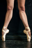 Close-up ballerina's legs in pointes on the black Royalty Free Stock Images