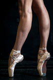 Close-up ballerina's legs in pointes on the black Stock Photos