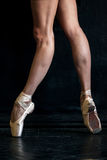 Close-up ballerina's legs in pointes on the black Royalty Free Stock Photos