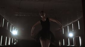 Close-up of ballet dancer as she practices exercises on dark stage or studio. Ballerina shows classic ballet pas. Slow. Motion. Flare, gimbal shot stock video