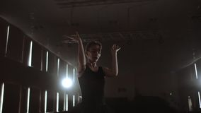 Close-up of ballet dancer as she practices exercises on dark stage or studio. Ballerina shows classic ballet pas. Slow. Motion. Flare, gimbal shot stock footage