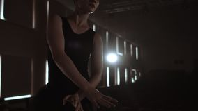 Close-up of ballet dancer as she practices exercises on dark stage or studio. Ballerina shows classic ballet pas. Slow. Motion. Flare, gimbal shot stock video footage