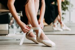 Close up for ballet dancer putting on, tying ballet shoes. Ballerina putting on her pointe shoes