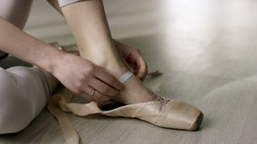 Close up for ballet dancer putting on, tying ballet shoes. Ballerina putting on her pointe shoes sitting on the floor. stock images