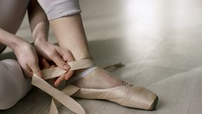 Close up for ballet dancer putting on, tying ballet shoes. Ballerina putting on her pointe shoes sitting on the floor.