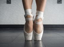 Close up of a ballet dancer`s bare feet in pointe shoes. In the dance studio during ballet class stock photos