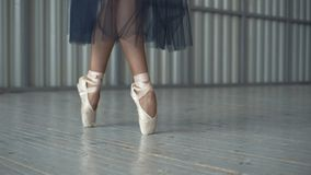 Close-up of ballet dancer`s legs in pointe shoes, tights and mesh skirt dancing on pointe in a choreography room. Ballet. Classes royalty free stock photo