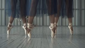 Close-up of ballet dancers legs in pointe shoes, tights and mesh skirt training in the choreography room on the wooden. Floor. Ballet classes stock images