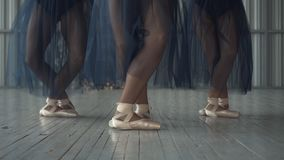 Close-up of ballet dancers legs in pointe shoes, tights and mesh skirt training in the choreography room on the wooden. Floor. Ballet classes stock photos