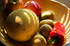 Close up bamboo fruit basket with melon, apples, kiwis, bell pepper illuminated by evening sun beams stock image