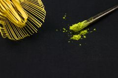 Close up bamboo whisk and matcha green tea powder on black. Background Stock Image