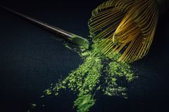 Close up bamboo whisk and matcha green tea powder on black Stock Photography