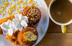 Close up Banana cup cakes with white sesame seeds and peanuts topping served with fresh coffee for breakfast. Banana cupcakes with white sesame seeds and stock image