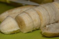 Close up of a banana with some banana slices. Photographed with macro lens and a blurred background Stock Image