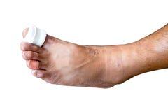 Close-up of a bandage wrapped on injured toe isolated over white. Close-up of a bandage wrapped on injured toe isolated over white royalty free stock image