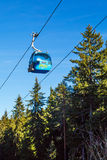 Close up Bansko cable car cabin, pine trees  against vibrant blue sky, Bulgaria Royalty Free Stock Images