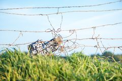 Close up of barbed wire fence with no trespassing sign on private ranch. Blurred green field with animals on background stock image