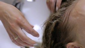 Close-up - barbeiro que lava os cabelos fêmeas antes de fazer um penteado vídeos de arquivo