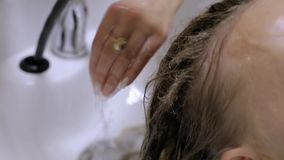 Close-up - barbeiro que lava os cabelos fêmeas antes de fazer um penteado video estoque