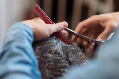 Close up of barber during haircut for grey-haired man Stock Photography