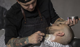 Barber preparing to shave the beard in the barbershop.Close up image royalty free stock photo