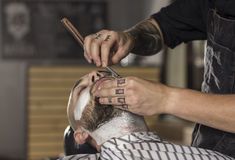 CLose up of Barber shaving client using old fashioned razor royalty free stock image