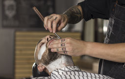 CLose up of Barber shaving client using old fashioned razor Stock Images