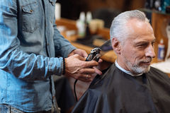 Close up barber trimming hair of old man Stock Images