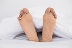 Close up of bare feet in bed Royalty Free Stock Photos