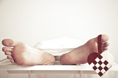 Close up of bare feet with checkered heart. Hanging from the big toe while white sheet drapes over the rest of the body Royalty Free Stock Images