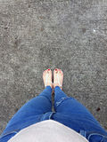 Close up of Bare Feet with Red Nail in Sandals and Blue Jeans Woman On The Concrete Floor Background. Great For Any Use Stock Photo
