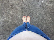 Close up of Bare Feet with Red Nail in Sandals and Blue Jeans Woman On The Concrete Floor Background. Great For Any Use Stock Images