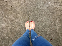 Close up of Bare Feet with Red Nail in Sandals and Blue Jeans Woman On The Concrete Floor Background. Great For Any Use Royalty Free Stock Photo