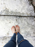 Close up of Bare Feet with Red Nail in Sandals and Blue Jeans Woman On The Concrete Floor Background. Great For Any Use Royalty Free Stock Images