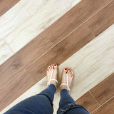 Close up of Bare Feet with Red Nail in Sandals and Blue Jeans Woman On The Tile Background. Great For Any Use Stock Images
